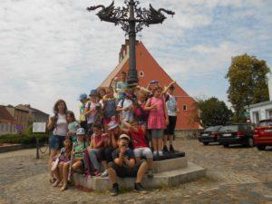 Duża grupa dzieci na cokole wokół kolumny.