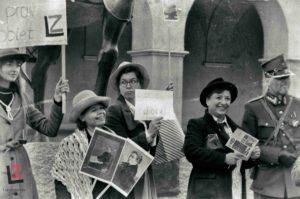 kobieta trzymająca w ręku dwa transparenty ze zdjęciami na kijach