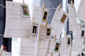 zawieszone na sznurkach wypisane formularze ze zdjęciami