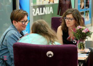 trzy kobiety prowadzą rozmowę siedząc na krzesłach