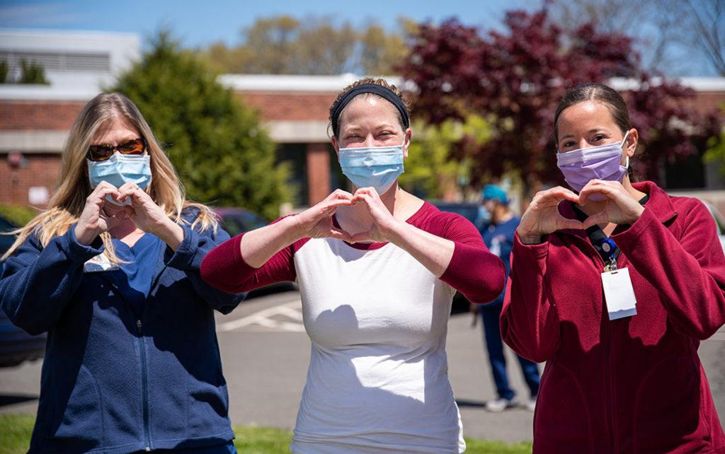 trzy kobiety w maseczkach układają ręce w kształcie serca