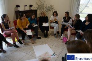 grupa kobiet siedząca w kręgu z kartkami w ręku