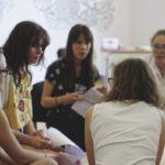 Grupa kobiet siedzi w kręgu i prowadzi ożywioną dyskusję.
