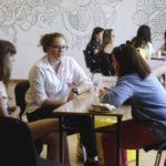 Dwie grupy osób siedzących przy stołach prowadzą rozmowę.