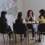 Cztery kobiety siedzące przy stole prowadzą rozmowę.