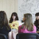 Grupa kobiet siedzi na krzesłach.