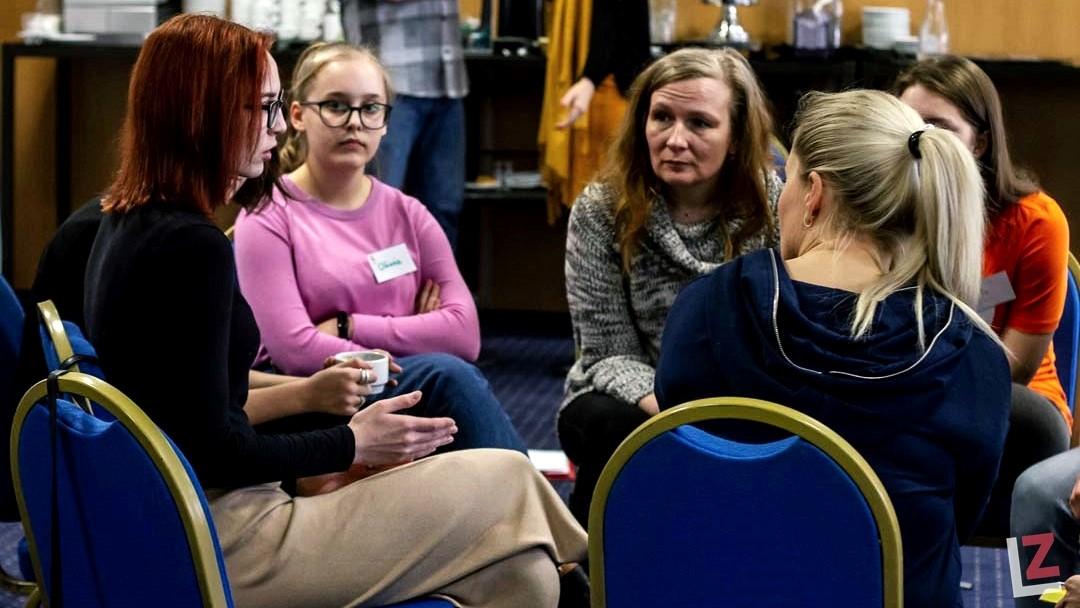 rozmowa kilku kobiet siedzących na krzesłach