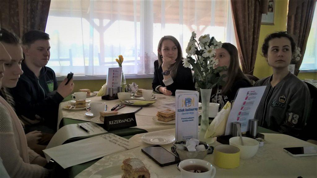 Cztery dziewczyny i chłopak siedzą w kawiarni przy zastawionym stole z napisem rezerwacja.