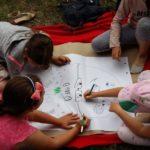 Trójka dzieci siedząca na kocu rysuje na dużym arkuszu papieru.