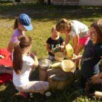 Pięć dziewczynek siedząc na trawie, przygotowuje ciasto w naczyniach leżących na pniu drzewa.