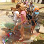 Trojka dzieci tańczy w kałuży farby boso, w tle grupa dzieci przygląda się im.