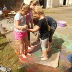 Cztery dziewczynki stoją w kałuży farby boso, trzymając się za ręce.