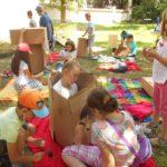 Na pierwszym planie dziewczynka siedząca w kartonie oraz trójka dziewczynek malująca ten karton. W tle grupa dzieci bawiąca się kartonami.