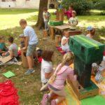 Duża grupa dzieci na trawie i kolorowych kocach buduje zamek z kartonów.