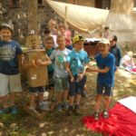 Grupa sześciu chłopców uśmiecha się wprost do obiektywu. Jeden chłopiec ubrany jest w karton. W tle grupa dziewczynek.