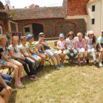Duża grupa dzieci siedząca na ławce w półokręgu. W tle zabudowania zamkowe