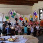 Duża grupa dzieci, młodzieży i dorosłych siedząca przy dużej drewnianej ławie. W tle za nimi rozwieszone na ścianie kolorowe plakaty.