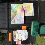 Czarna, lśniąca drewniana ława, na której leżą kolorowe obrazki malowane kredkami przez dzieci.