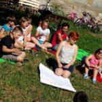 Duża grupa dzieci siedząca na trawie wokół młodej kobiety z dużym arkuszem papieru.