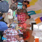 Grupa dorosłych i dzieci siedząca przy stole. Nad nimi wiszą arkusze papieru z rysunkami ubrań.
