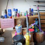 """Na szafce stojące kolorowe kubki i butelki z dużą kartką podpisana """"Kreatywne instrumenty muzyczne""""."""