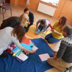 Pięć kobiet i mężczyzna, siedząc na podłodze, wycinają ozdoby z kolorowego papieru.