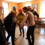 Grupa dorosłych w koronach na głowach z papieru kolorowego stoi w kręgu.