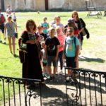 Grupa dzieci z dwoma opiekunkami stoi na placu przy zamku.