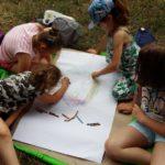 Cztery małe dziewczynki rysują kredkami na dużym arkuszu papieru, siedząc na kocu.