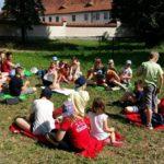 Bardzo duża grupa dzieci siedząca na kocach na trawie podczas słonecznej pogody.