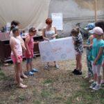 Grupa kilku dzieci wraz z kobietą trzyma duży plakat z różnymi napisami, który same zrobiły.