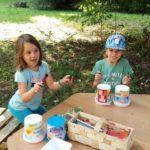 Dwie małe dziewczynki trzymające w rękach mazaki siedzą na ławce przy stoliku, na którym stoi koszyk po truskawkach i plastikowe kubki.