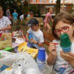 Na pierwszym planie dziewczynka i dwóch chłopców ozdabiający plastikowe kubki. W tle duża grupa dzieci.
