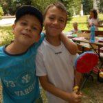 Na pierwszym planie dwóch uśmiechających się chłopców trzymających zabawkę. W tle dwie dziewczynki.