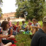 Duża grupa dzieci siedząca na trawie.