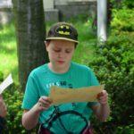 chłopczyk w czapce ze znakiem batmana trzyma w rękach kartkę papieru