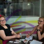 Dwie młode dziewczyny siedzą uśmiechnięte przy stoliku i grają w karty.