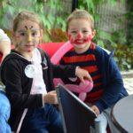 Dwójka dzieci, chłopiec i dziewczynka z pomalowanymi farbkami twarzami bawią się balonem.