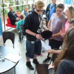 Grupa młodzieży stoi w holu muzeum i spogląda na kartkę papieru. Na bocznym planie widać stół z kartami do gry.