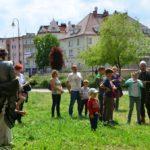 Grupa dzieci, młodzieży i dorosłych przygląda się, jak mała dziewczynka strzela z luku.