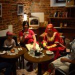 Mężczyzna, dwie kobiety oraz dwie małe dziewczynki siedzą przy kawiarnianych stolikach w pomieszczeniu ze ścianami ceglanymi o zamkowym wyglądzie.