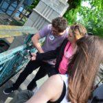 Dwie dziewczyny i trzech chłopaków stoją na moście, na którym przywieszone są kłódki zakochanych. Jedna z dziewczyn robi zdjęcie kłódce.