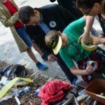 Chłopczyk w czapce ze znakiem batmana z pomocą dwójki dorosłych okleja taśma kawałek plastiku.