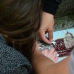Na zdjęciu dłonie trzech osób układające puzzle z wizerunkiem bazyliki.