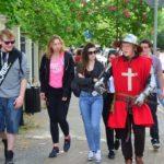 Grupa dziewczyn i chłopaków spaceruje ulica. Jeden z chłopaków ubrany jest w strój rycerski zakonu maltańskiego z czerwonym płaszczem i białym krzyżem.