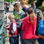 Dwójka chłopców trzyma w rękach kłódkę przypięta do mostu, asystuje im młoda kobieta.