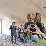 graffiti na murze kobiety pokazującej rękoma serce