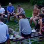 grupa osób siedząca w kręgu przy ognisku