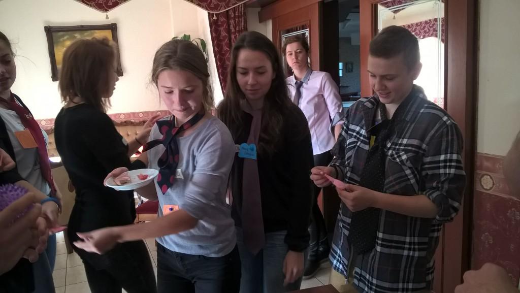 Na pierwszym planie dwie dziewczyny, z których jedna trzyma talerzyk oraz chłopak czytający karteczkę samoprzylepną. W tle trzy dziewczyny.