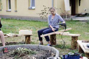 kobieta siedząca na ławce przy kręgu do ogniska z pomocą wiertarki zespala drewniane elementy.
